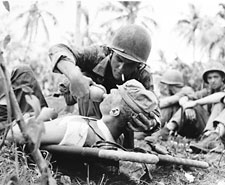 Image: Navy corpsman give drink to wounded marine on Guam